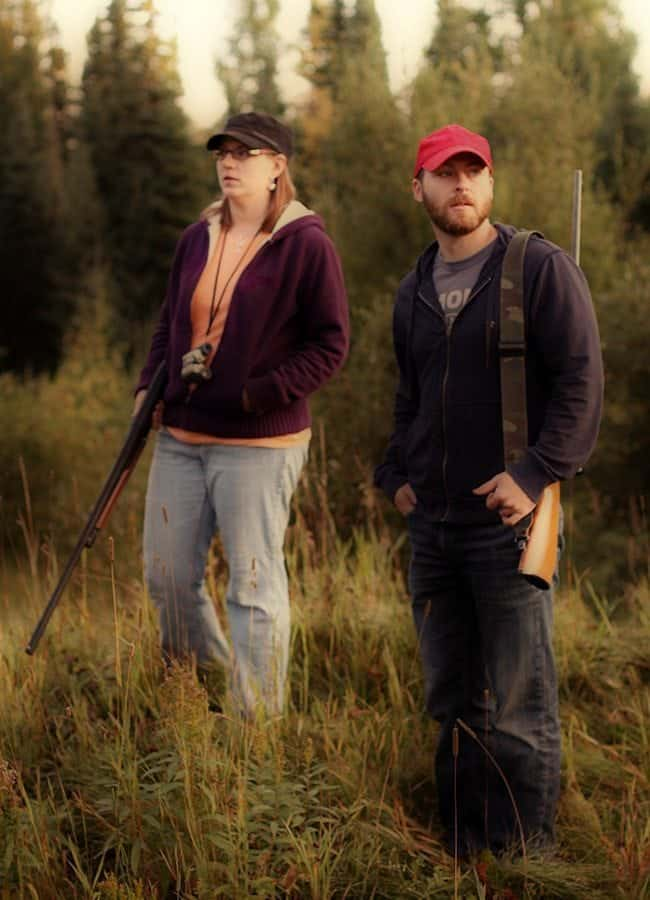 Woman and man standing in the woods with guns looking for animals