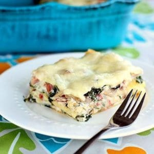 Cheesy Ham & Kale Lasagna serving in a white plate with fork