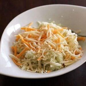 Creamy Mozza, Creamy Herb & Garlic and Creamy Mexicana shredded cheese in a white bowl
