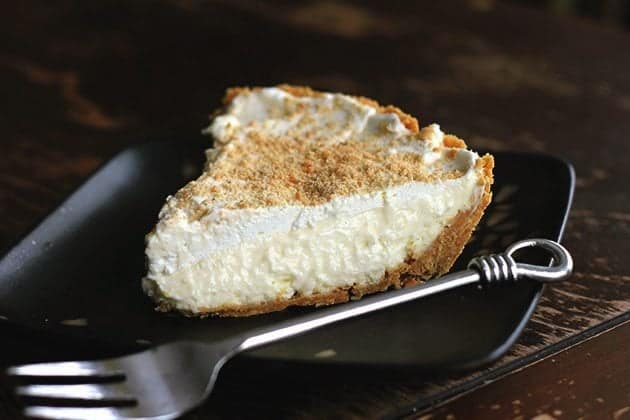close up of lemon cream pie slice in black plate