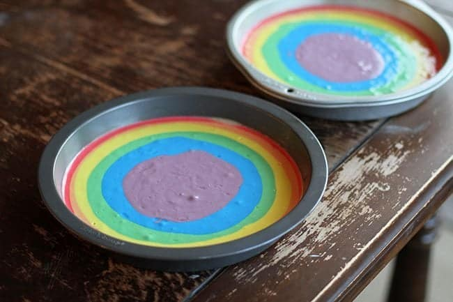2 cake tins with rainbow color batter