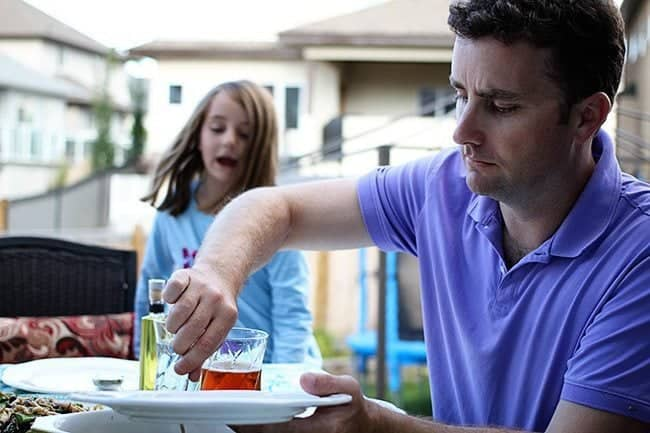 man in blue polo shirt preparing something in white plate with young girl at the back so excited