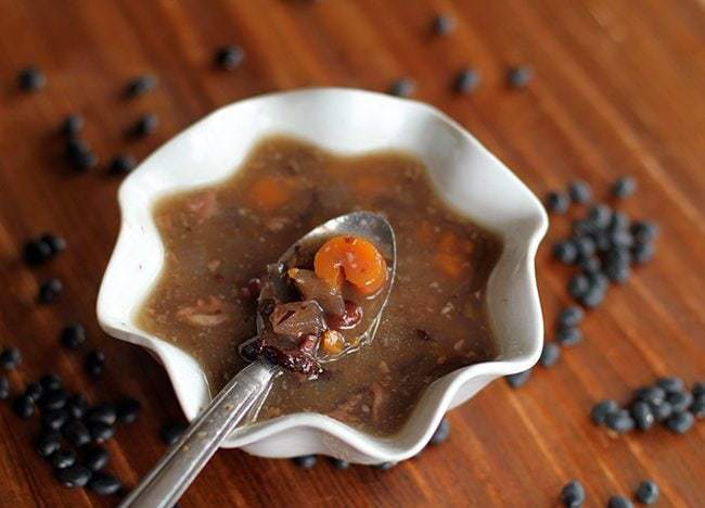 Black Bean & Ham Soup in a White Ruffle Bowl with Spoon, some black beans on background