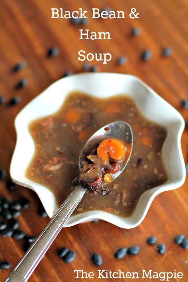 Top Down shot of Black Bean & Ham Soup in a White Ruffle Bowl with Spoon, some black beans on background