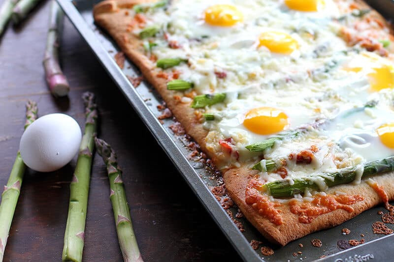 Fresh egg and asparagus beside the pan with Breakfast Pizza
