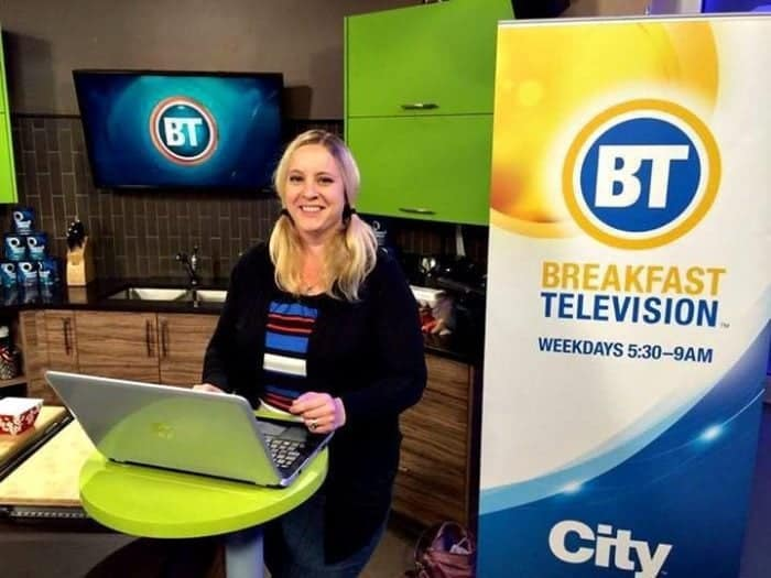woman standing with her laptop on the table in Breakfast Television set up
