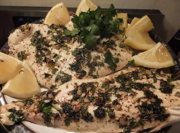 Garlic & Herb Fish with slices of lemon and chopped cilantro
