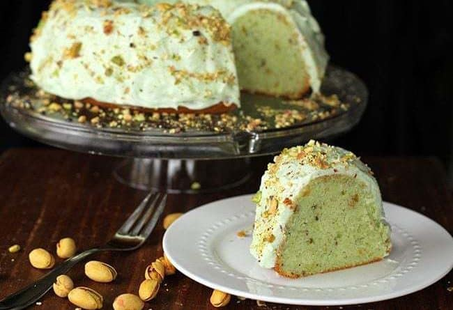 Close up of Homemade Pistachio Pudding Cake with Pistachio Buttercream Frosting in transparent cake holder and a slice in white plate