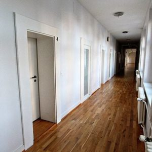 long narrow hallway inside the hotel with walls painted white