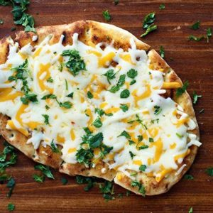 Top down shot of Tex Mex Cheesy Grilled Naan Bread sprinkled with chopped cilantro in a wood background