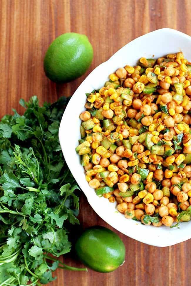 Top down shot of Roasted Corn & Chickpea Salad on a white square bowl, a bundle of Cilantro beside it