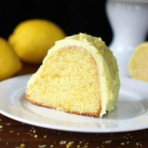 a slice of Homemade Lemon Pudding Cake in White plate, fresh lemons on background