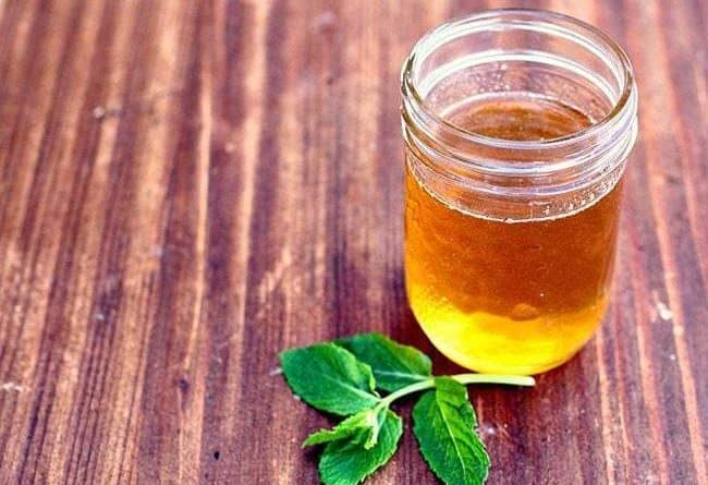 Mint Honey Simple Syrup in a glass container, mint leaves on wood background