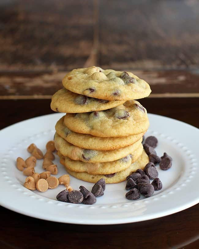 Stack of Peanut Butter and Chocolate Banana Pudding Cookies in white plate with chocolate chips