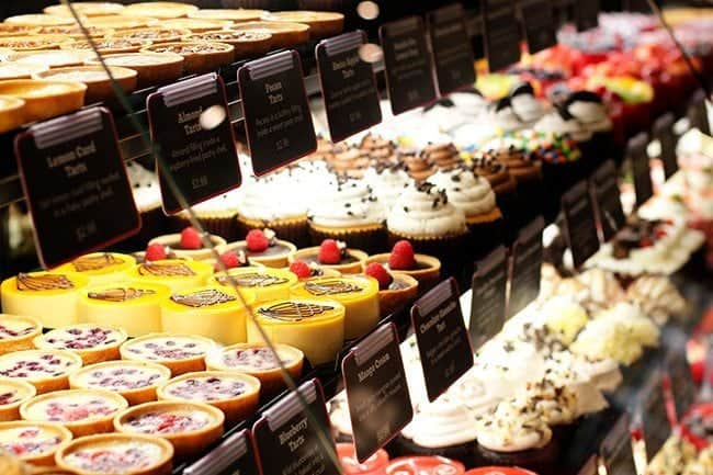 close up of tarts, cakes and cupcakes in the bakery section