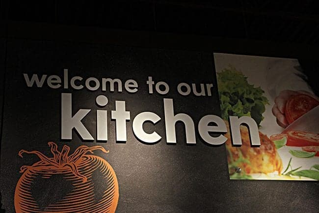 Black wall with the signage of Welcome to our Kitchen