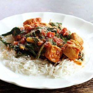 close up of Rice topped with Curried Chicken With Wilted Swiss Chard on a white plate