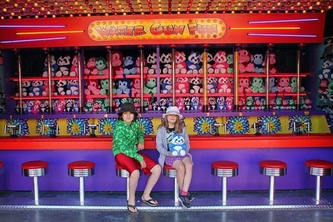 two kids sitting in front of water game fun booth holding her prize stuffed panda
