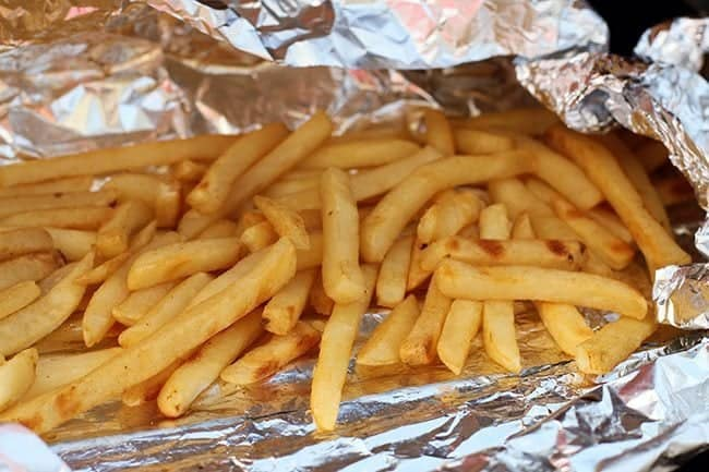 fries placed in a cooking oil sprayed tin foil packet