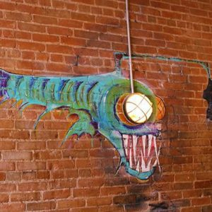 red brick wall with piranha like painting figure