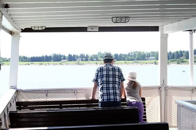 dad and his daughter standing in the boat watching the ocean