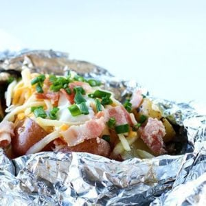 close up Campfire Grilled Loaded Baked Potatoes in a tinfoil topped with onion, cheese, sour cream, salt and pepper