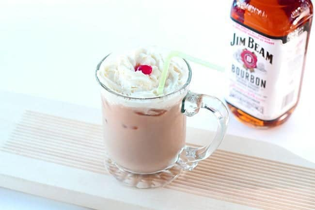 A glass of Bourbon Paralyzer topped with whipped cream and cherry. A bottle of Jim Beam brand bourbon at the back.