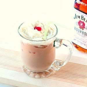 A glass of Bourbon Paralyzer topped with whipped cream and cherry