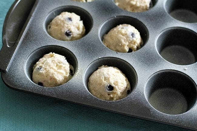filling up the muffin tins with scoops of cookie dough