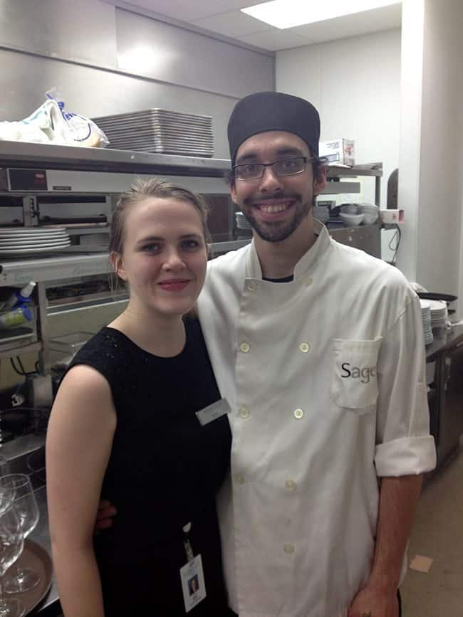 a lady black dress and a chef with beard at the kitchen