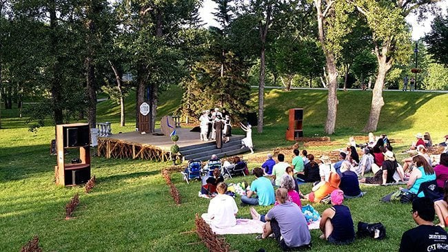 families sitting in the picnic area of the park watching the play at the stage