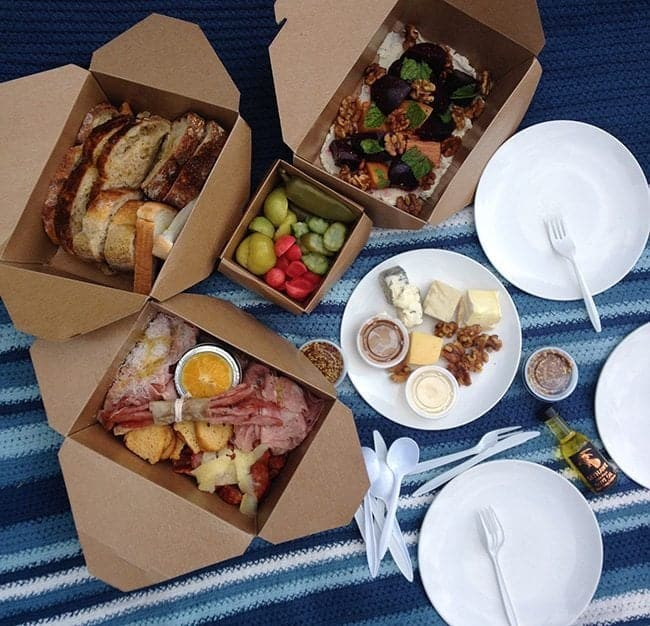 boxed foods, fruits and white plate in a picnic matt