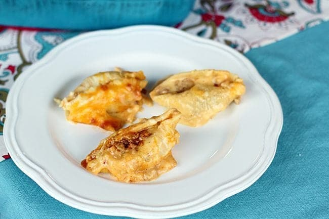 3 pieces of Cheesy Taco Stuffed Shells in a white plate on jade blue tablecloth background