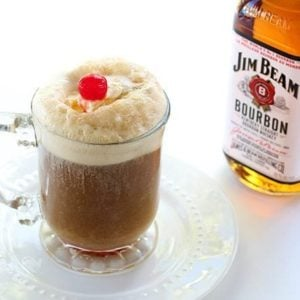 close up of glass of Bourbon Root Beer Ice Cream Floats with whipped cream and cherry. A bottle of Jim Beam bourbon at the back.