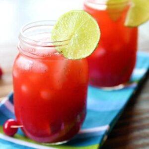 close up Cherry & Raspberry Bourbon Lemonade on mason jars garnish with a slice of lemon