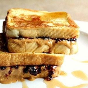 white plate with Peanut Butter & Jelly French Toast with syrup drizzled on top