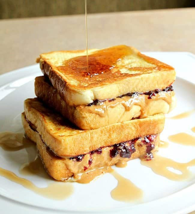 Syrup drizzled on top Peanut Butter & Jelly French Toast in a white plate
