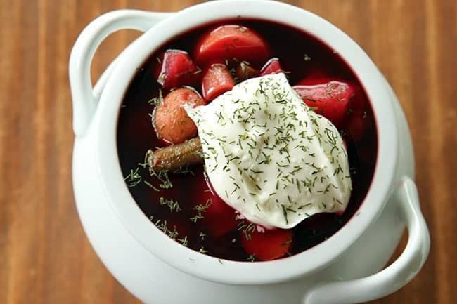 close up of chunky Ukrainian Borscht topped with sour cream and dill on brown background
