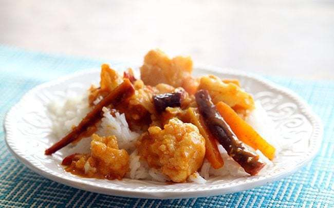 close up Curried Cauliflower and Carrots over rice in a white plate