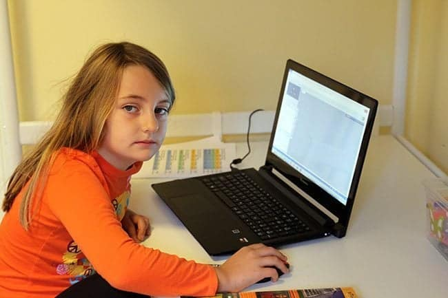 a young girl sitting, facing the laptop and holding the mouse
