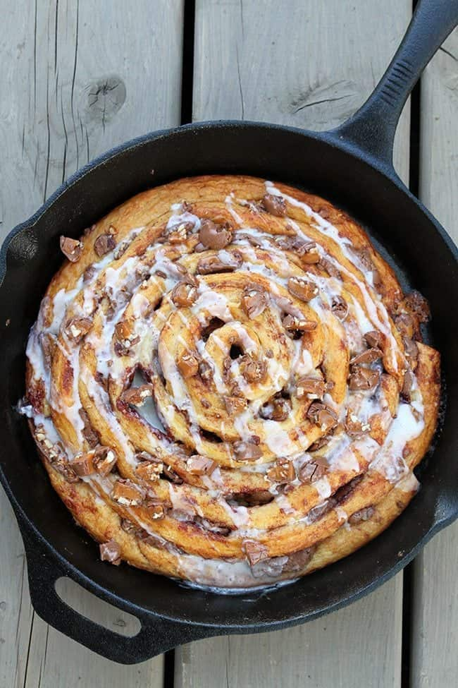 close up of Two Ingredient Giant Turtles Cinnamon Bun in a skillet on wood background