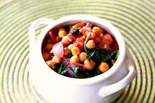 Spinach, Tomato & Chickpea Stew in a white pot like bowl on a spiral background