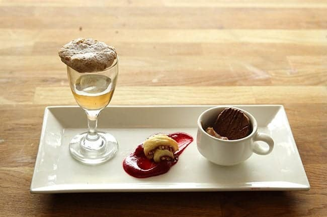 a small dessert plate with a glass of champagne, Italian Amaretti and Raspberry Rugulah Pinwheels
