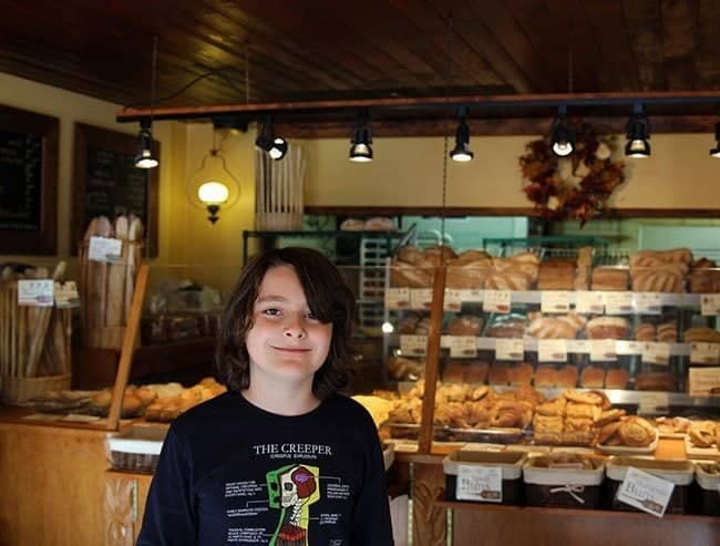 young boy's picture inside the bakery with lots of bread on his background