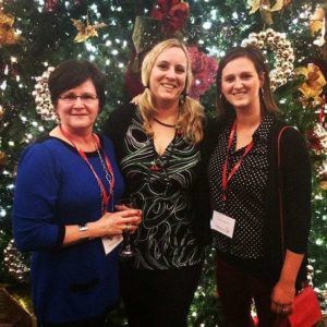 group picture of three ladies in front of tall Christmas tree