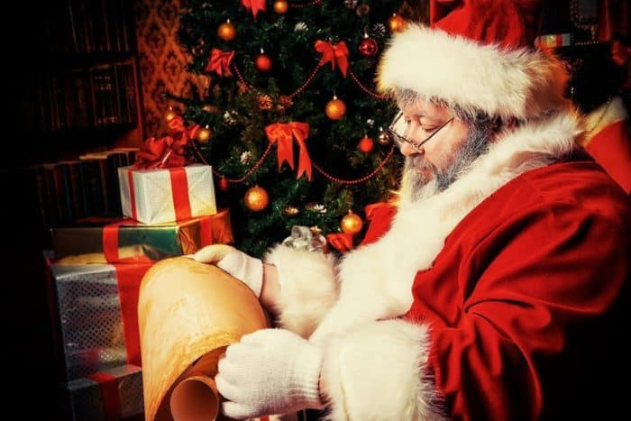 Santa Claus sitting in a room decorated for Christmas, and reading his list