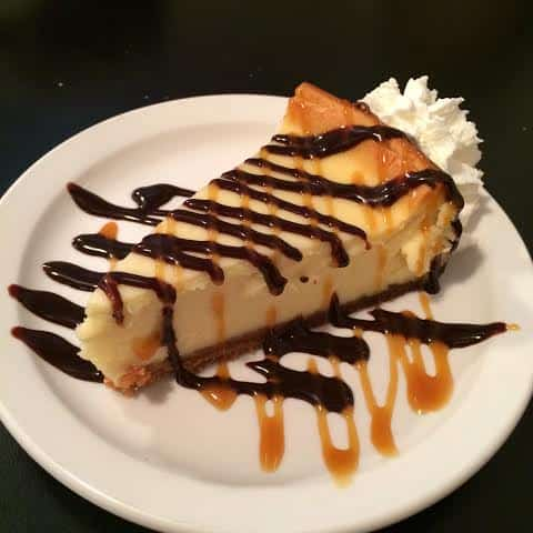 white plate with Diner Cheesecake topped with chocolate and caramel syrup