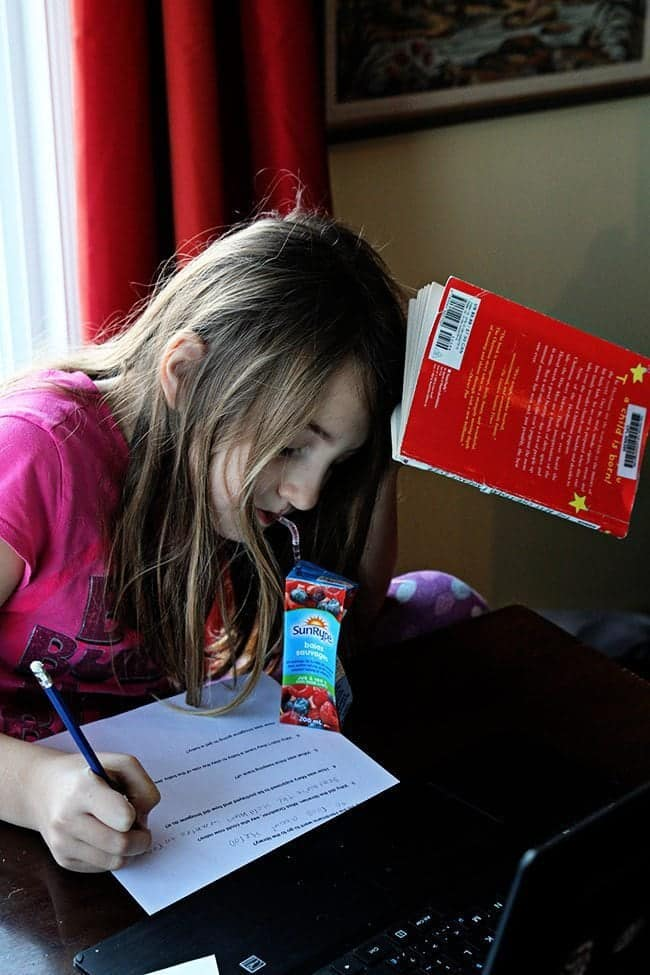 young girl sipping from a box juice while studying and a book was in her head