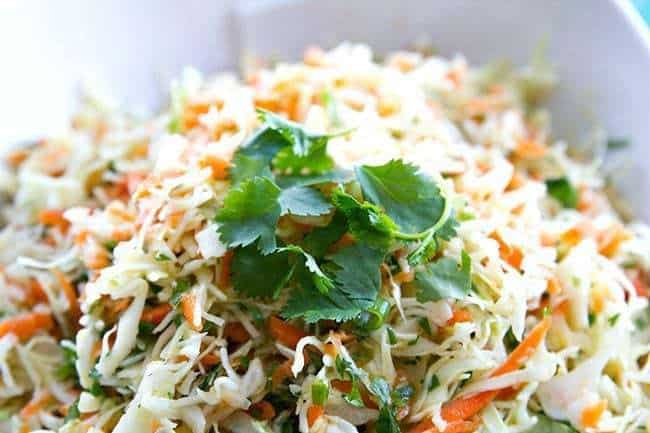 Simple Mexican Crispy Coleslaw with lime and garlic dressing garnish with parsley