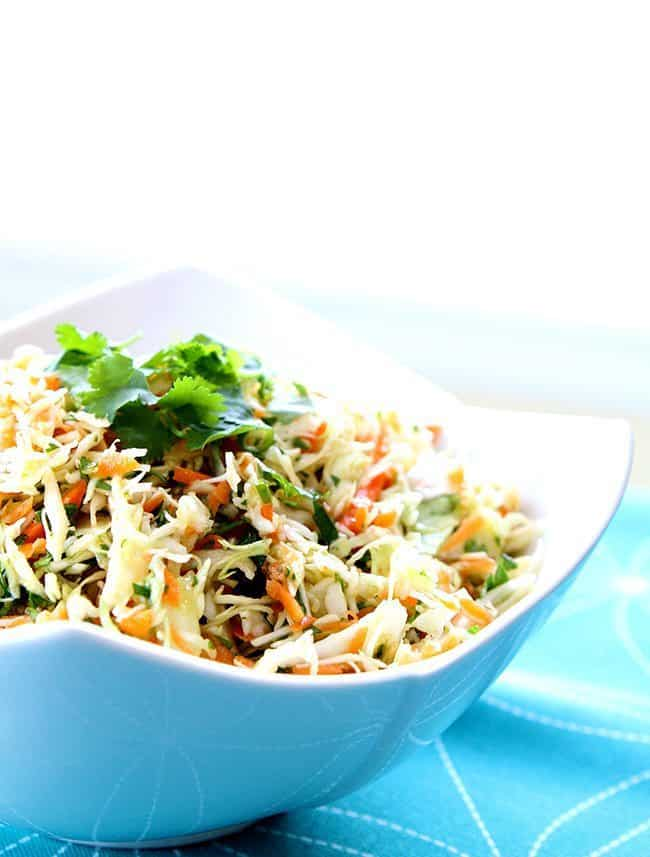 Mexican Coleslaw with lime and garlic dressing garnish with parsley in a Blue Pyrex bowl